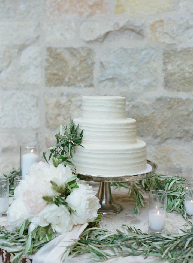 Elegant understated three tier wedding cake with natural florals and greenery against a warm stone backdrop at Sunstone Winery - photo by Elizabeth Messina. #weddingcakes #simplelegance #weddingideas #wineryweddings