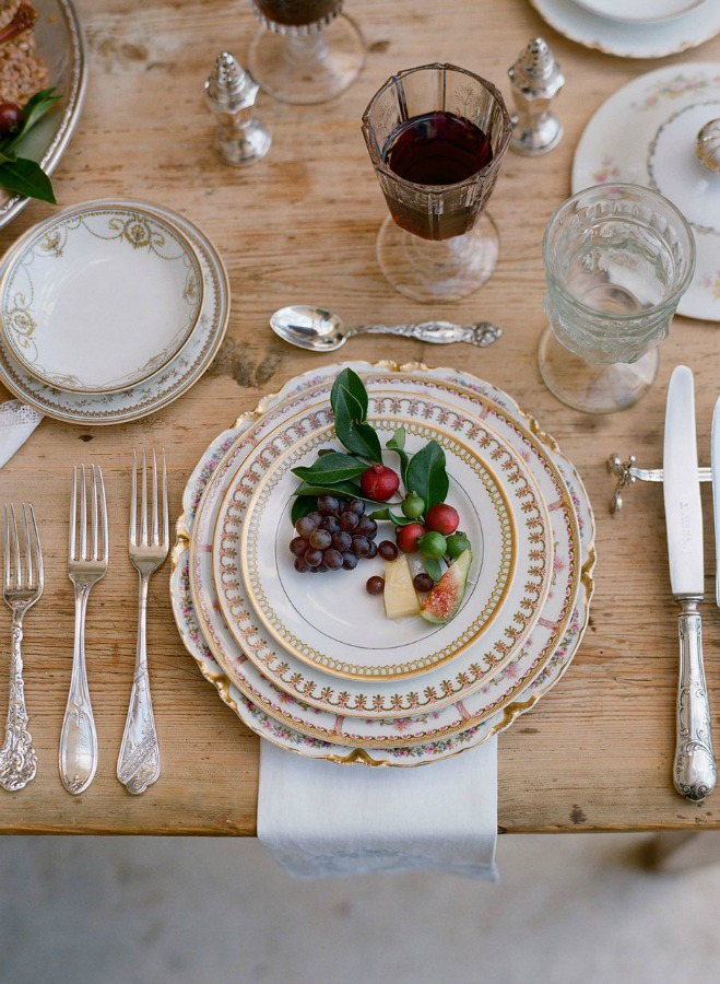 Vintage china in an elegant placesetting at a rustic farm table - rich and elegant tablescape inspiration - photo by Elizabeth Messina. #placesetting #romantictablescape #vintagestyle