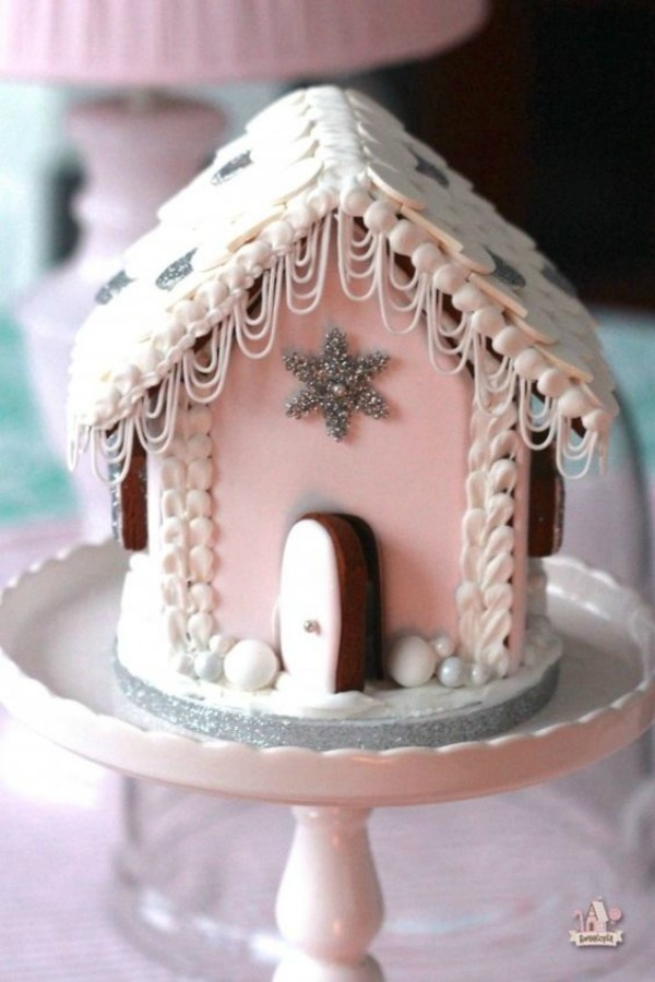 Charming pink gingerbrread house on a pedestal. #pinkchristmas #christmasbaking #gingerbreakhouse #candyhouse