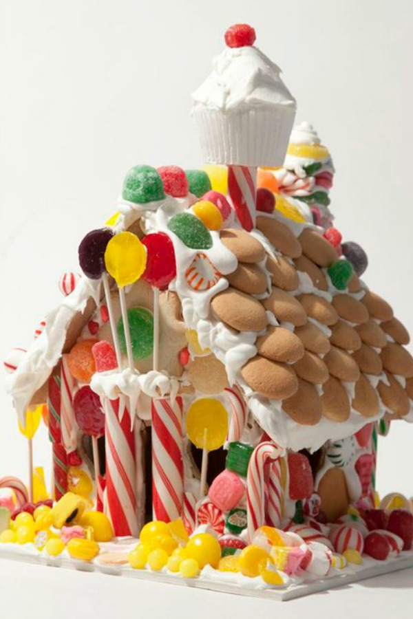 Cupcake chimney on a fanciful candy house decorated with vanilla wafers. #gingerbreadhouse #christmasbaking #holidaydiy