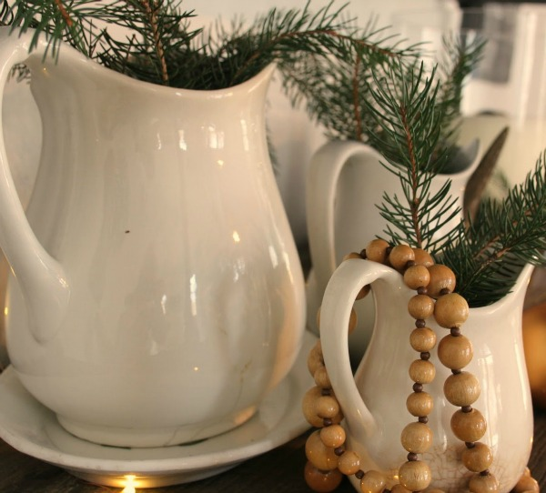 White Christmas decorated ironstone pitchers with fresh greenery in my home - Hello Lovely Studio. #hellolovelystudio #ironstone #christmasdecor