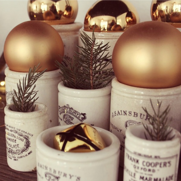 Vintage marmalade jars with greenery and gold bulbs in my Christmas home - Hello Lovely Studio. #christmasdecor #hellolovelystudio #vintagechristmas
