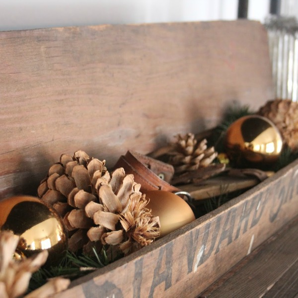 Rustic vintage wood box filled with pinecones and gold Christmas balls - Hello Lovely Studio.