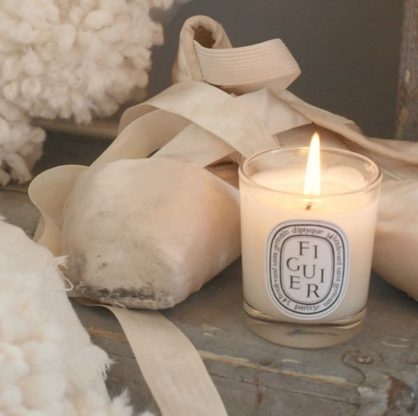 White Christmas decor vignette with Diptyque candle, pom pom wreaths and ballet slippers - Hello Lovely Studio. #christmasdecor #pompomwreath #christmaswreath #pinkchristmas