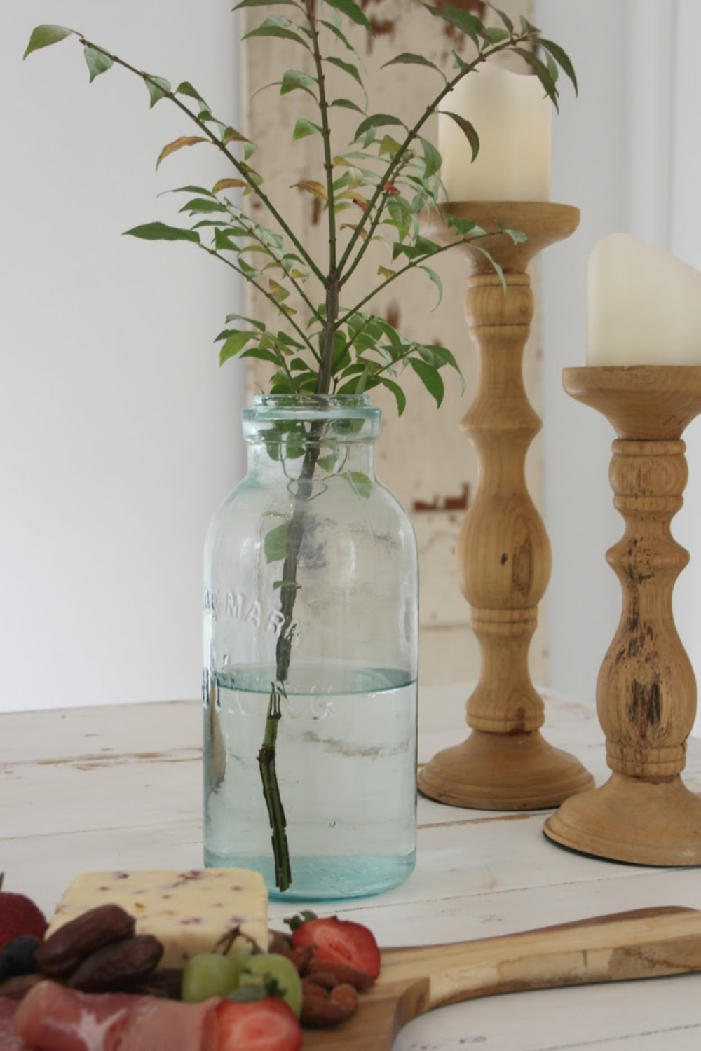 Hello Lovely Studio serene vignette with branch and rustic candle holders. Come score ideas for a Timeless and Tranquil European Country Inspired Look. #europeancountry #interiordesign #frenchcountry