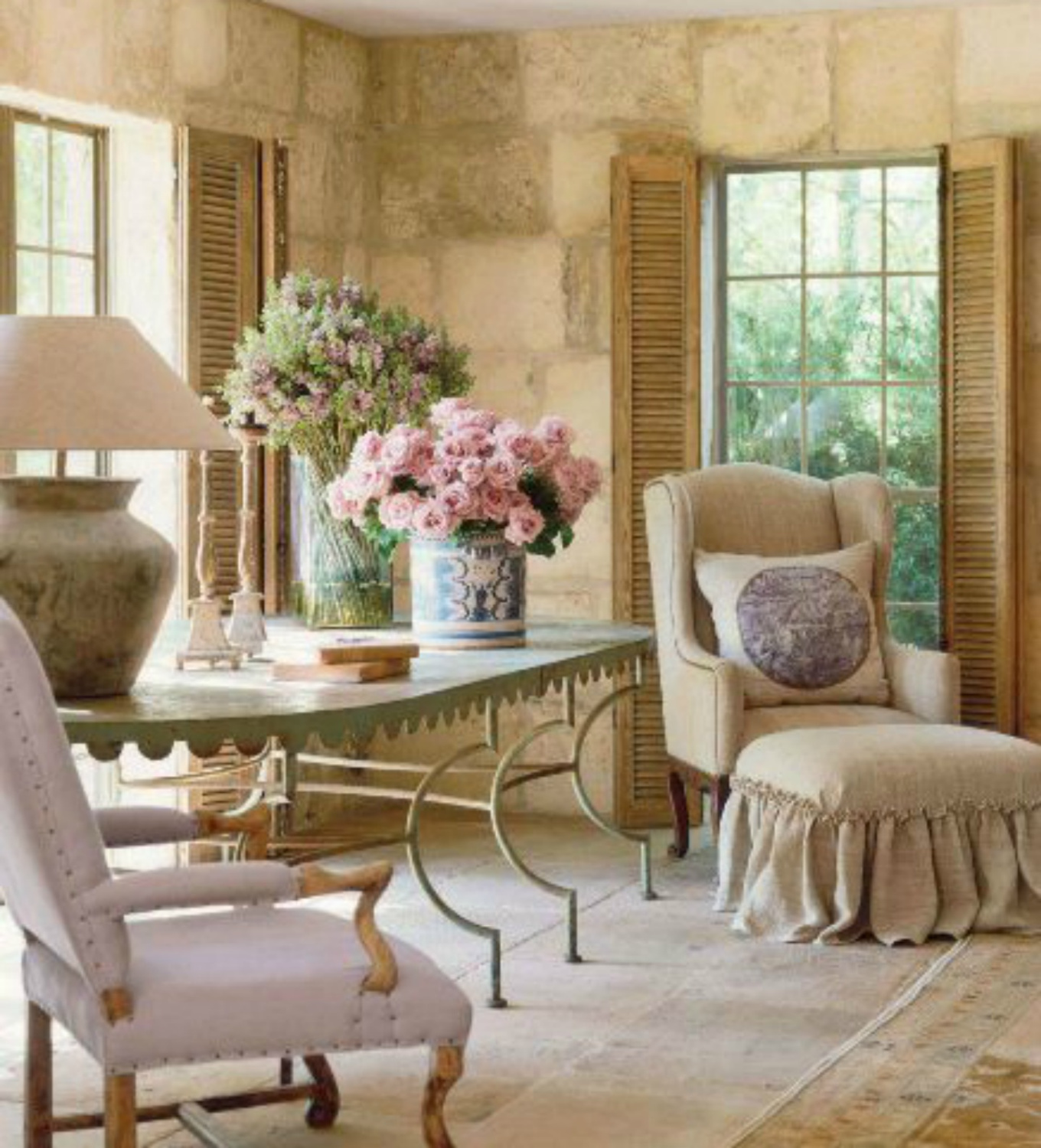 French farmhouse living room with antiques, limestone, and shutters on Hello Lovely Studio #chateaudomingue #Frenchfarmhouse #PamelaPierce
