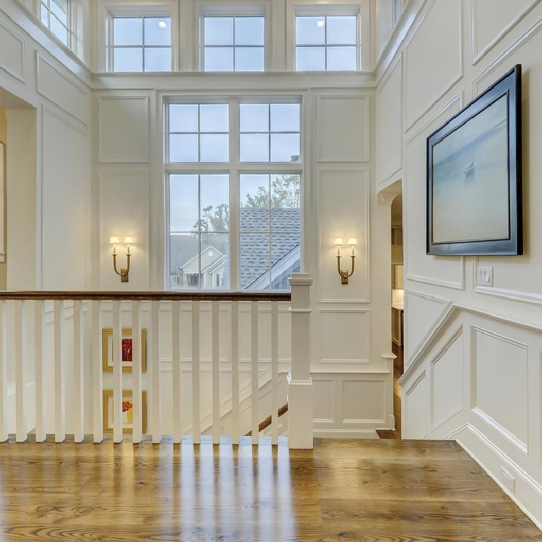 Benjamin Moore Simply White painted paneling and trim in a beautiful traditional stairway landing - Susan Joyce Design. #simplywhtie #benjaminmooresimplywhite #whitepaintcolors