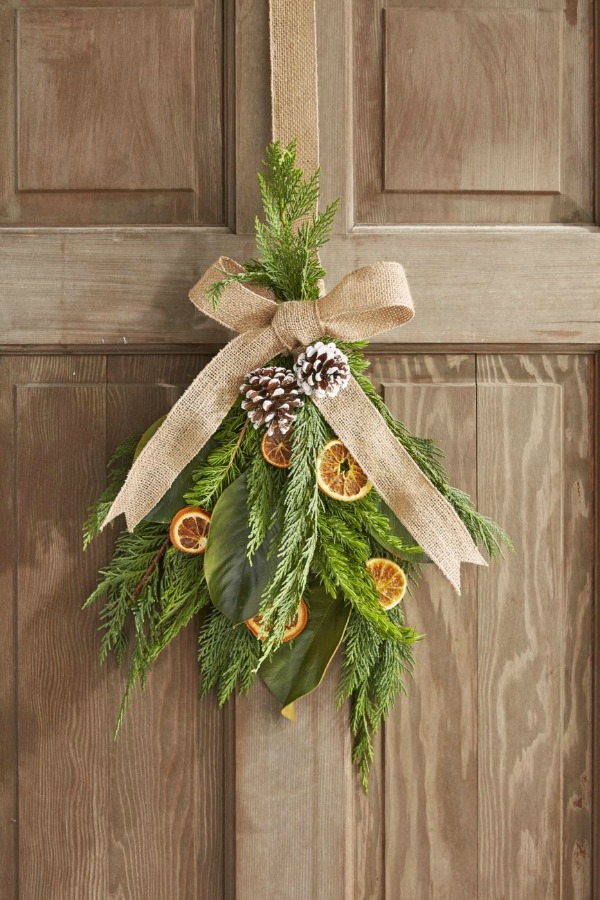 Dried oranges in a Christmas swag on door with greenery and pinecones - Country Living. #christmasdecor #handmadedecor #greenery #driedoranges