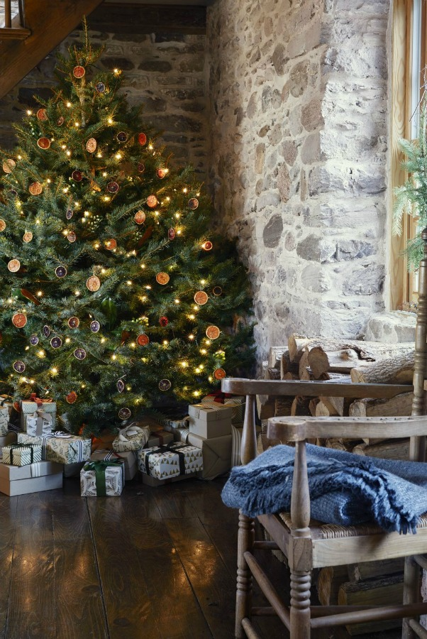 Dried oranges on a Christmas tree in a lovely room with rustic stone wall - Country Living. #christmastree #driedcitrus #garlands #countrychristmas