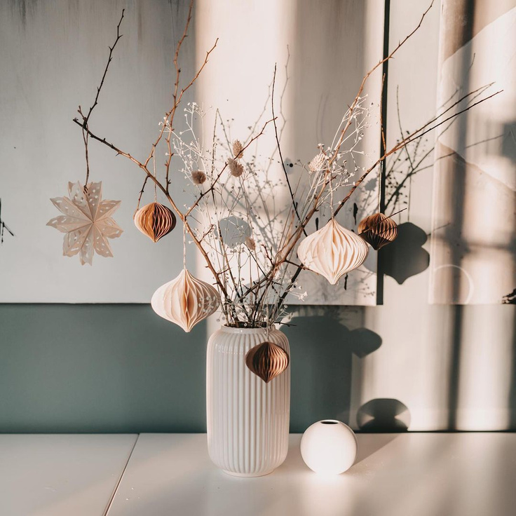 Lovely handmade paper Scandi ornaments dangle from bare branches in a vase for this holiday moment by Herzenseinrichtung.