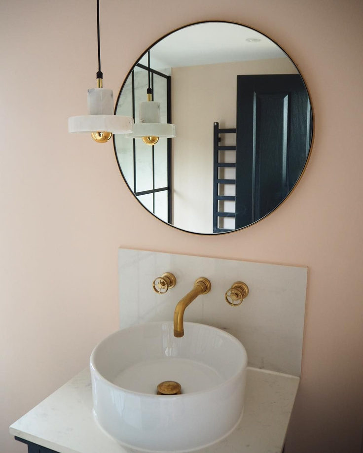 Farrow & Ball Pink Ground paint color on walls of a lovely powder room with vessel sink, brass taps, and round mirror - HouseLust.