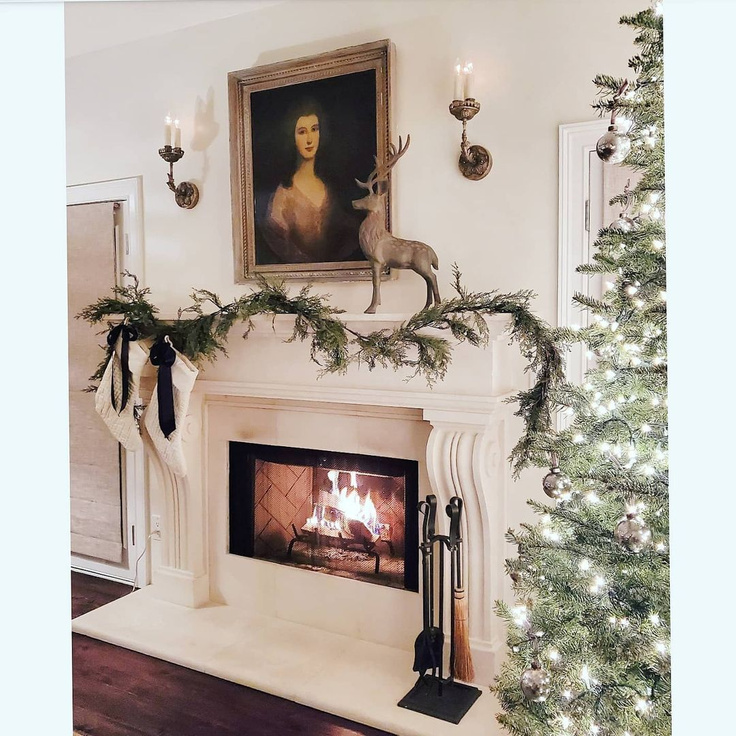 Elegant French country Christmas decorated living room with fireplace, portrait, stag, greenery, and white stockings - TheFrenchNestCoInteriorDesign.