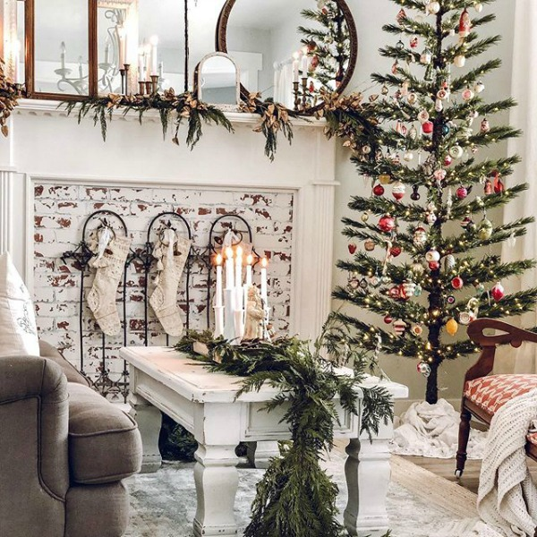 White farmhouse Christmas decorated living room with vintage design elements - Le Cultivateur. #holidaydecor #christmasdecor #livingroom #farmhousechristmas #whitechristmas
