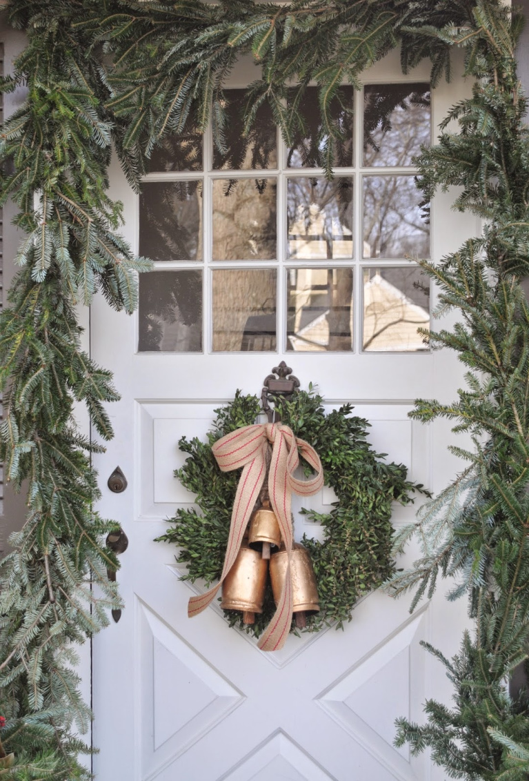 Charming and rustic Christmas wreath with gold toned bells and ribbon upon a white country door framed with fresh greenery - NineandSixteen.