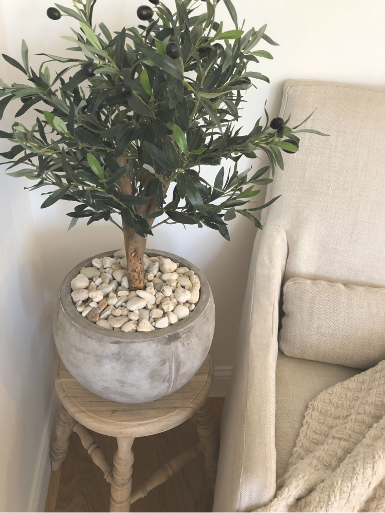 Stunning olive tree in rustic pot on teak farmhouse stool with Belgian linen chair in my breakfast room - Hello Lovely Studio.