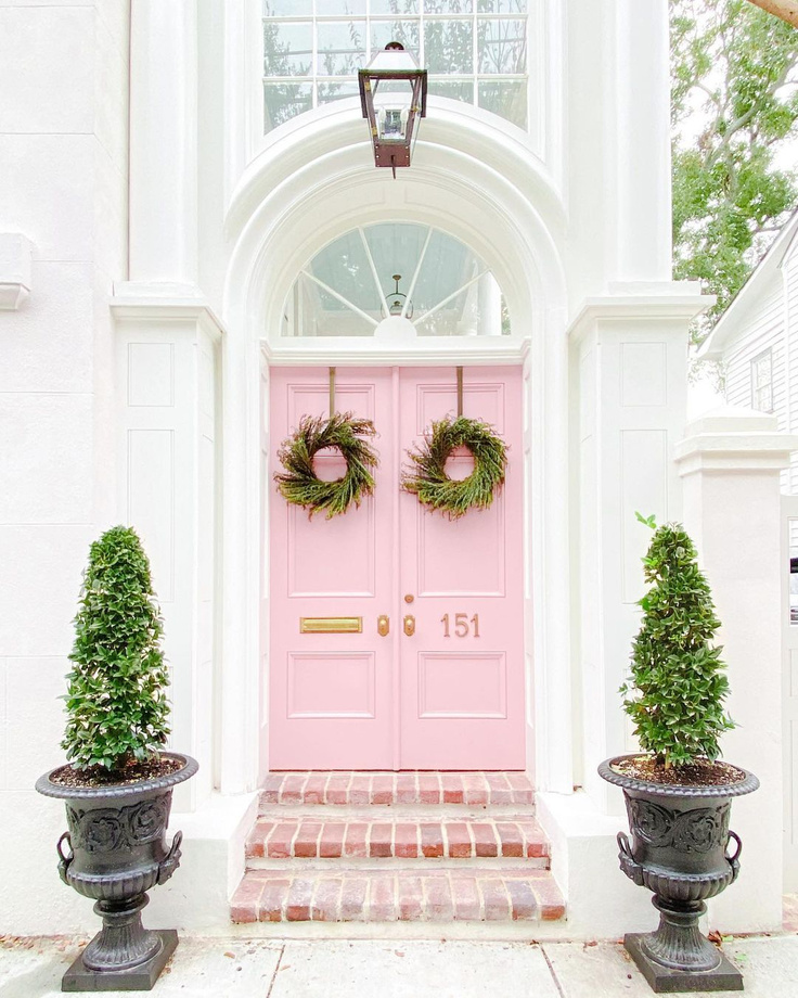 Gorgeous fresh pink painted doors with Christmas wreaths on a Charleston home - @sarahweisbrod