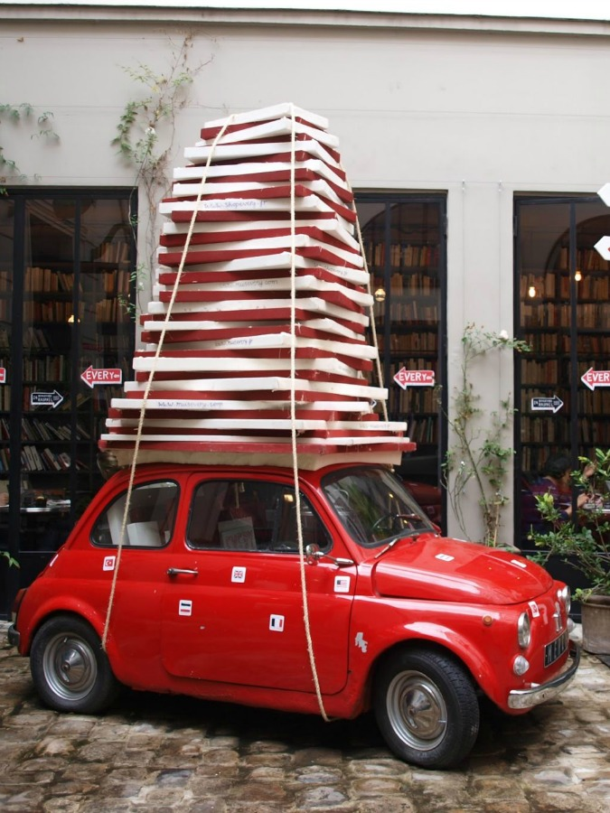 Vintage European red tiny car piled high with packages in front of Merci boutique in Paris - Hello Lovely Studio. #merciboutique #parisshop #vintagecar #redcar