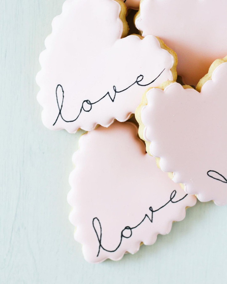 "Beautiful scalloped edged heart cookies with ""love"" by TinyCrumbsCookieCo."