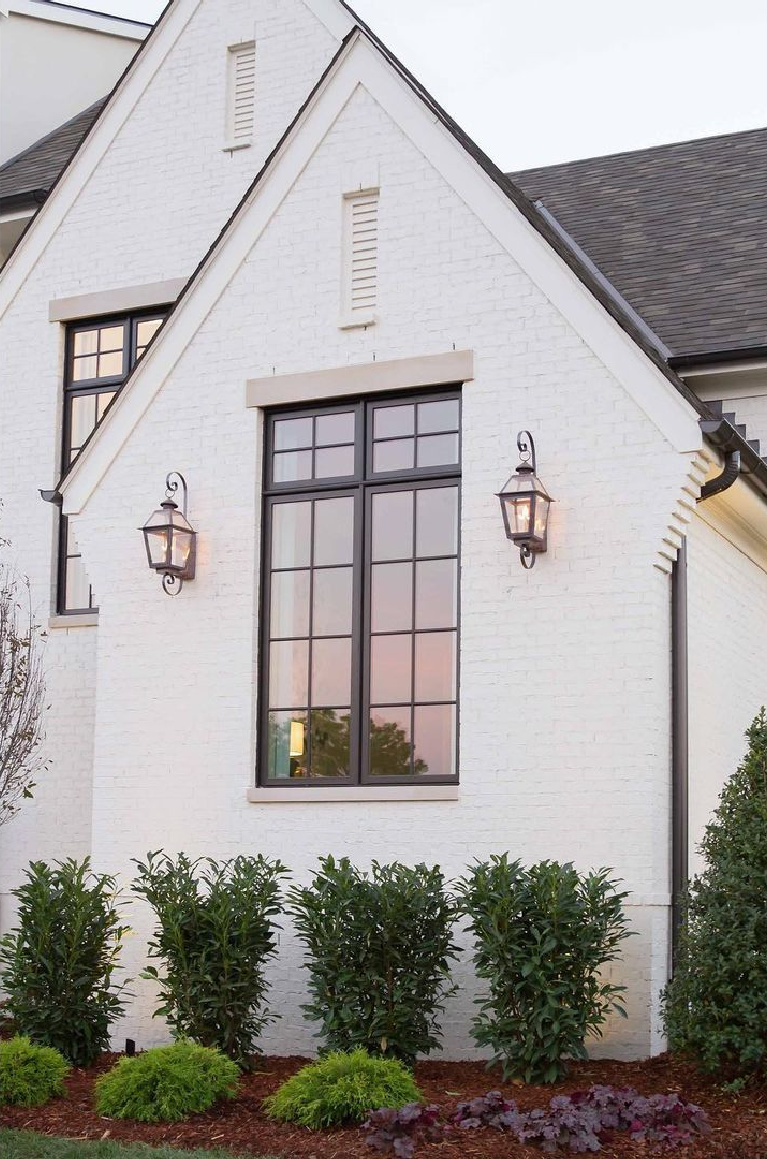 White brick house exterior with Shoji White (Sherwin Williams), design by @mrsparanjape and photo by Kristen Mayfield. #shojiwhitepaint #shojiwhite #whitepaintcolors #whitebrick