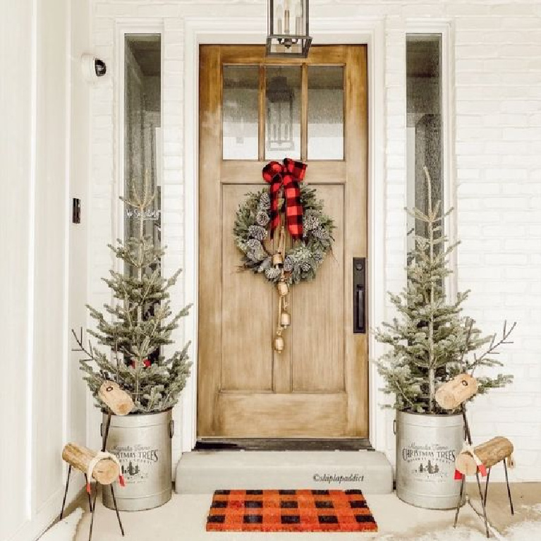 Charming farmhouse Christmas porch with galvanized planters with trees and vivid red buffalo checks - ShiplapAddict. #christmasporch #porchdecor #christmasdecorations #buffalocheck