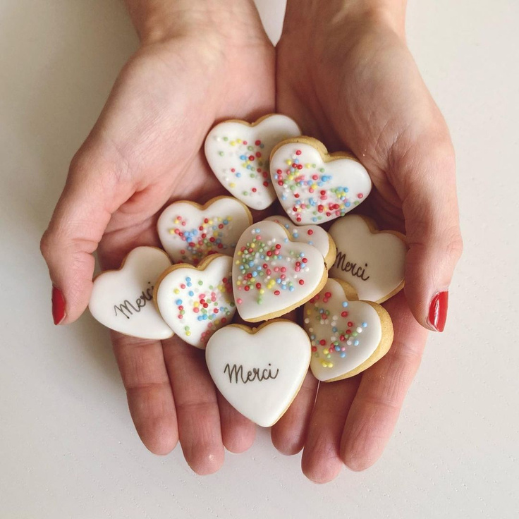 "Tiny frosted heart cookies with sprinkles and ""merci"" in hands - @biscuitz_biarritz."