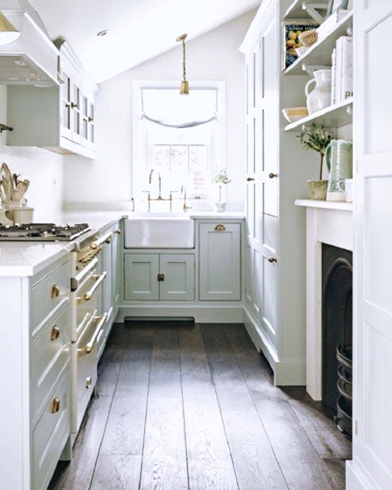 Charming and tiny white French farmhouse cottage style galley kitchen with fireplace and farm sink. #whitefrench #cottagekitchens #tinykitchens #galleykitchen #countrykitchen