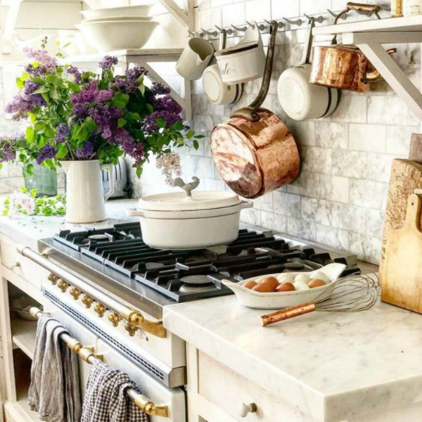 White Country french farmhouse decor inspiration in a kitchen with Lacanche range, white marble, and copper pots. #dreamywhites #fernchcountrykitchen #frenchkitchen #frenchfarmhouse #interiordesign #kitchendesign