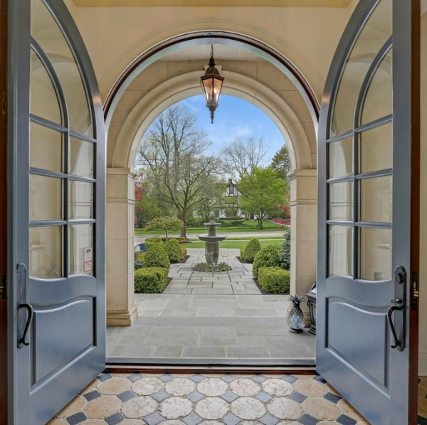 Arched French door entry in a magnificent French country mansion in Hinsdale, Illinois. #frenchcountry #luxuryhome #entry #archeddoors