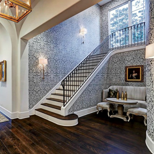 Farrow & Ball Silvergate wallpaper near staircase in an elegant French country mansion in Houston by Thomas O'Neill Homes.