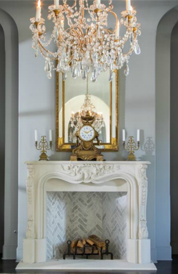 Elegant French mantel and crystal chandelier in a Houston mansion with French country design. #frenchfireplace #oldworldstyle #interiordesign #frenchcountry