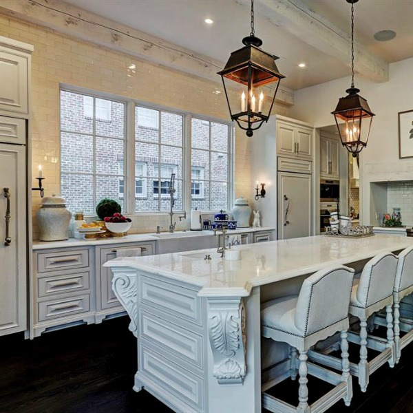 Luxurious white French country kitchen with lantern pendants and white cabinets in a Houston manse by TOH. #frenchcountry #kitchendesign #whitekitchens #elegantdecor