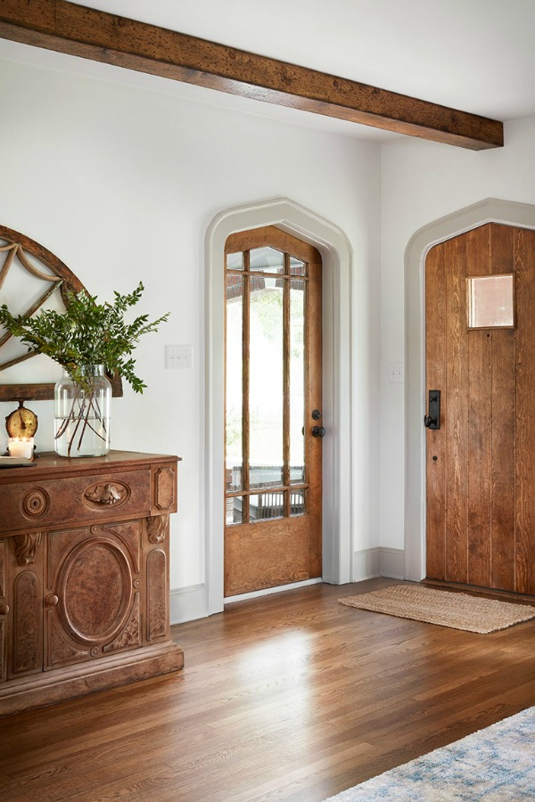 Beautiful entry!  Come get inspired by Tranquil and Timeless Tudor Design Details From a Serene 1920s Texas Cottage renovated on HGTV's Fixer Upper by Chip and Joanna and known as the Scrivano House. #fixerupper #scrivano #cottagestyle #interiordesign #greytrim #serenedecor #entry #cottages