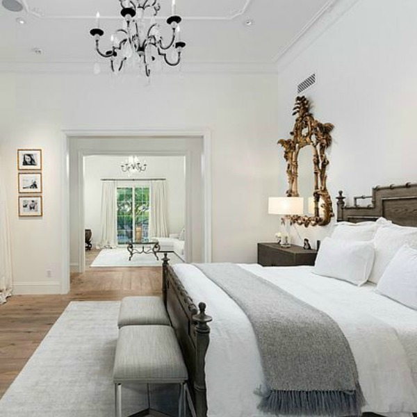Beautiful white luxurious French bedroom with gallery white walls, gilded mirror, and sitting area. #bedroomdesign #whitebedroom #frenchcountry #interiordesign
