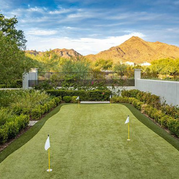 Luxurious mountain view backyard with putting green at a classic French inspired Scottsdale home.