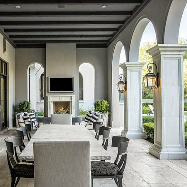 Beautiful loggia with archways, lanterns, dining table and fireplace at a French country Scottsdale home.