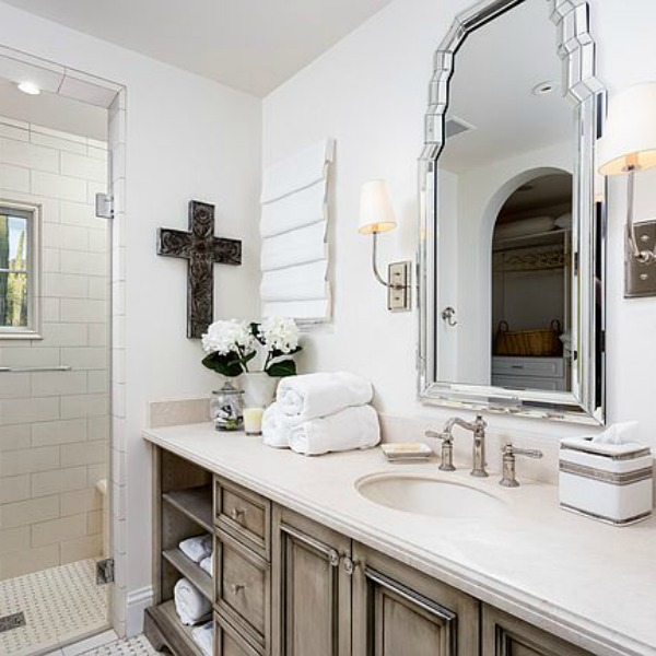 Beautifully designed French farmhouse white bathroom with antiqued vanity and cross on wall.PLEASE COME SEE Traditional Style Bathroom Vanity Design Inspiration as well as Vintage Bath Ideas. #bathroomdesign #bathroomvanities #interiordesign