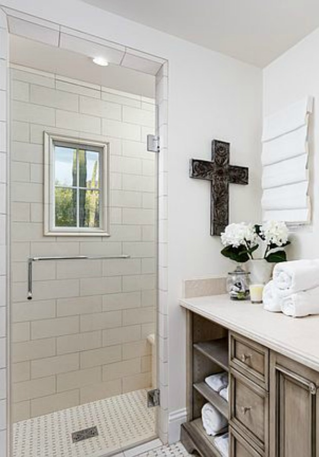 Beautifully designed French farmhouse white bathroom with antiqued vanity and cross on wall. #frenchcountry #bathroomdesign #whitebathroom