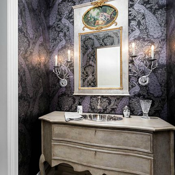 Elegant powder bath with black peacock wall covering, French country vanity, and charming sconces. #powderbath #frenchcountry #luxuriousbathroom