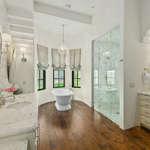 Luxurious and sophisticated white marble French inspired bathroom with freestanding tub and warm wood flooring. #luxuriousbathroom #bathroomdesign #frenchcountry