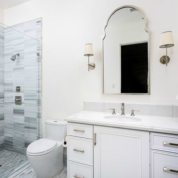 Classic white bathroom with white vanity and French inspired mirror and sconces. #whitebathroom #frenchcountry #bathroomdesign