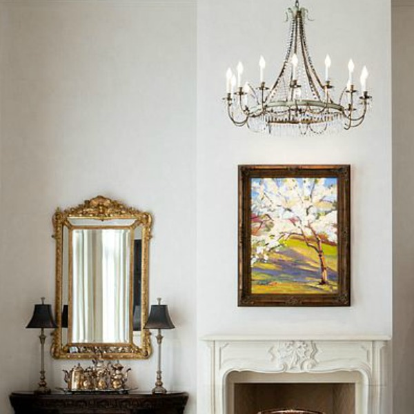 Gilded mirror, crystal chandelier, and French mantel in an elegant Scottsdale home.