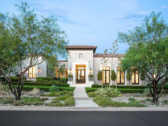 Classic, elegant luxurious house exterior in Scottsdale with tile roof, stucco, and French doors. #houseexterior #luxurioushome #scottsdalehome