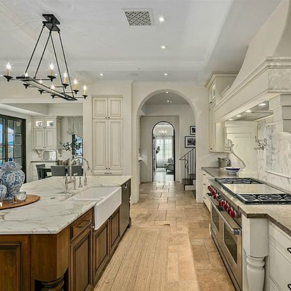 Elegant French country kitchen in luxurious Scottsdale home with stone floor, two tone cabinets, farm sink, and arch doorways. #luxuriouskitchen #frenchcountrykitchen #elegantdecor #kitchendesign