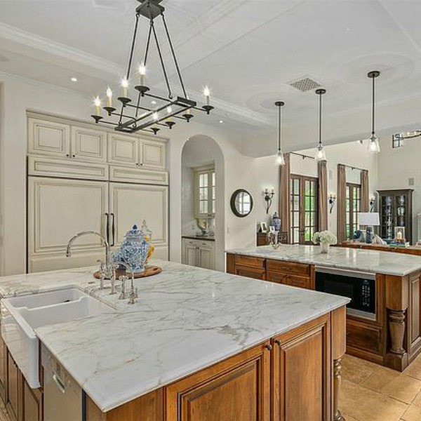 Double islands in elegant French country kitchen in luxurious Scottsdale home with stone floor, two tone cabinets, farm sink, and arch doorways. #luxuriouskitchen #frenchcountrykitchen #elegantdecor #kitchendesign
