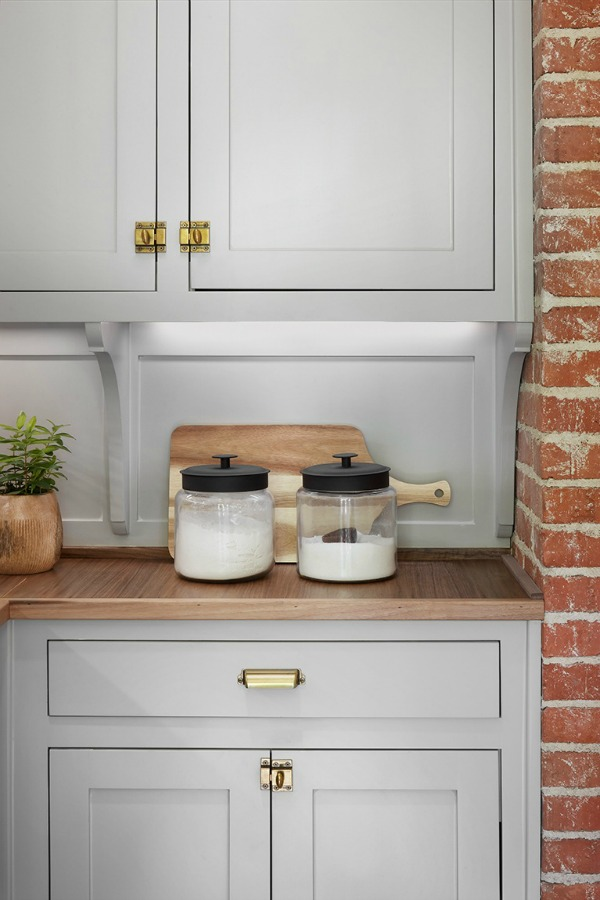 Gorgeous grey kitchen cabinets! This tranquil Tudor cottage was renovated on HGTV's Fixer Upper by Chip and Joanna and is known as the Scrivano House. #fixerupper #scrivano #cottagestyle #interiordesign #greytrim #serenedecor