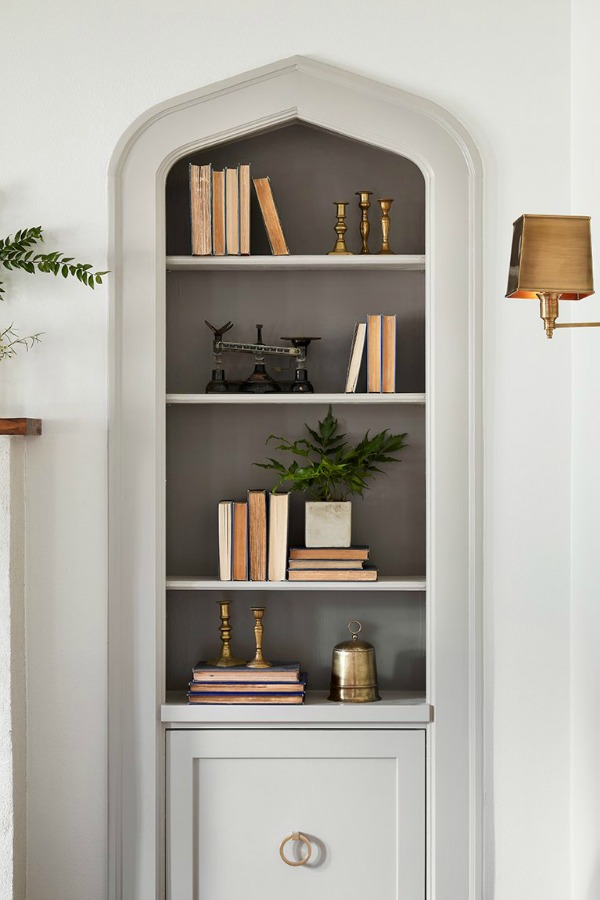 Built-in book shelves in living room.  Come get inspired by Tranquil and Timeless Tudor Design Details From a Serene 1920s Texas Cottage renovated on HGTV's Fixer Upper by Chip and Joanna and known as the Scrivano House. #fixerupper #scrivano #cottagestyle #interiordesign #greytrim #serenedecor #builtin #bookshelves #livingroom