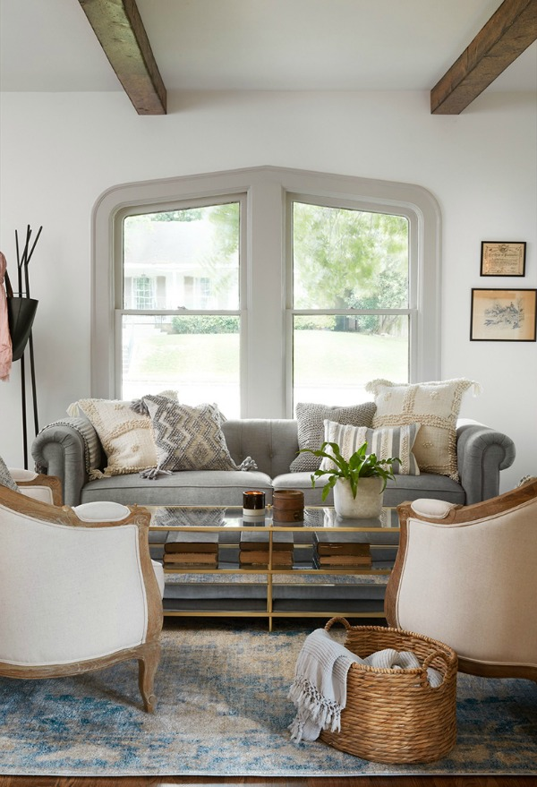 Serene living room with soft greys and white.  Come get inspired by Tranquil and Timeless Tudor Design Details From a Serene 1920s Texas Cottage renovated on HGTV's Fixer Upper by Chip and Joanna and known as the Scrivano House. #fixerupper #scrivano #cottagestyle #interiordesign #greytrim #serenedecor #livingroom #tudorcottage