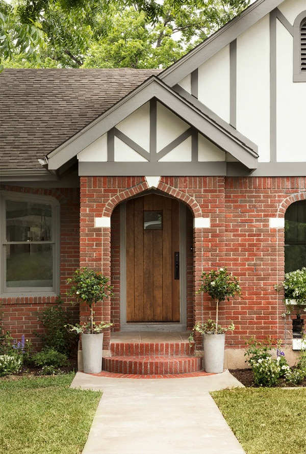 Brick Tudor exterior.  Come get inspired by Tranquil and Timeless Tudor Design Details From a Serene 1920s Texas Cottage renovated on HGTV's Fixer Upper by Chip and Joanna and known as the Scrivano House. #fixerupper #scrivano #tudorcottage #cottageexterior #homeexteriors