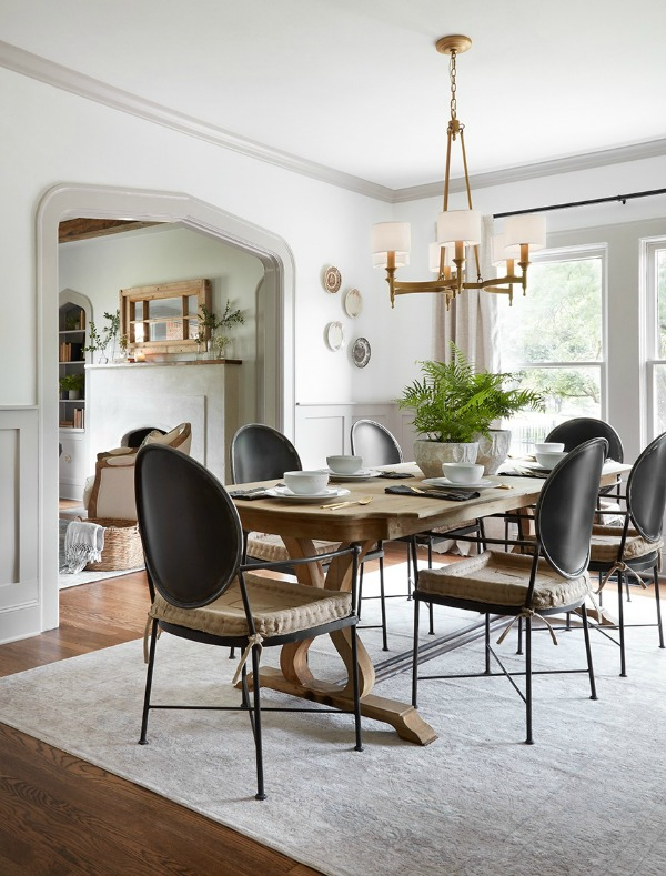 Dining room with modern Louis black chairs and farm table.  Come get inspired by Tranquil and Timeless Tudor Design Details From a Serene 1920s Texas Cottage renovated on HGTV's Fixer Upper by Chip and Joanna and known as the Scrivano House. #fixerupper #scrivano #cottagestyle #interiordesign #greytrim #serenedecor #diningroom