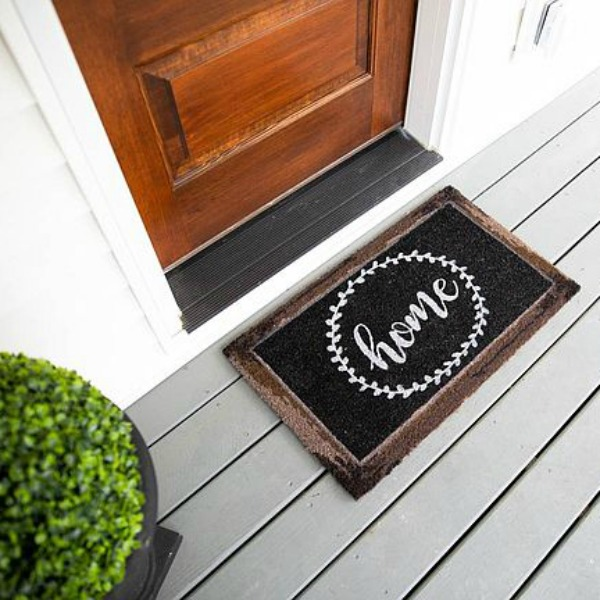 Whimsical black and white door mat at entrance to urban farmhouse with rustic wood door. #frontdoor #urbanfarmhouse #doormat #blackandwhitedecor